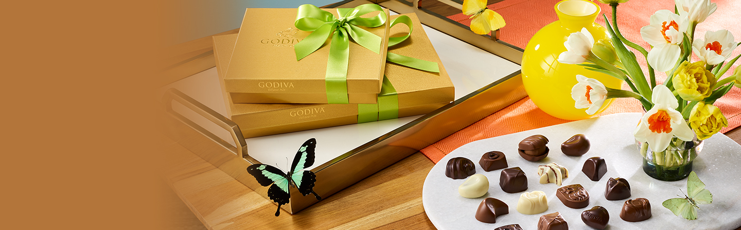 Gold gift boxes with green ribbon next to plate of chocolates