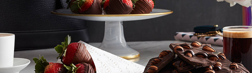 Chocolate covered strawberries on pedestal and in cone alongside chocolate bark