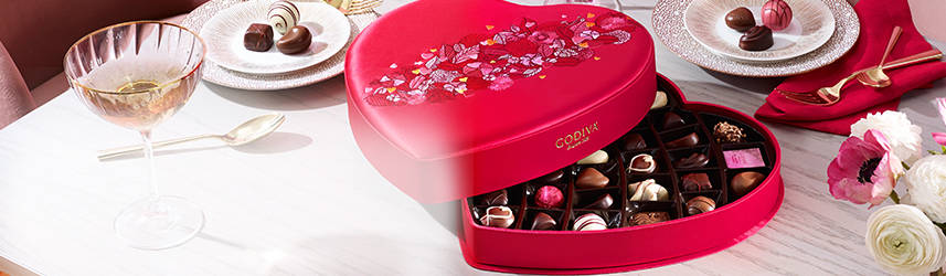 Open satin heart gift box alongside dessert plates with chocolate pieces