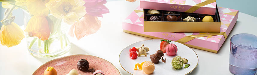 Stacked spring gift boxes with plate of chocolate pieces